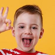 nino-emocionado-pie-mostrando-gesto-bien_171337-16369